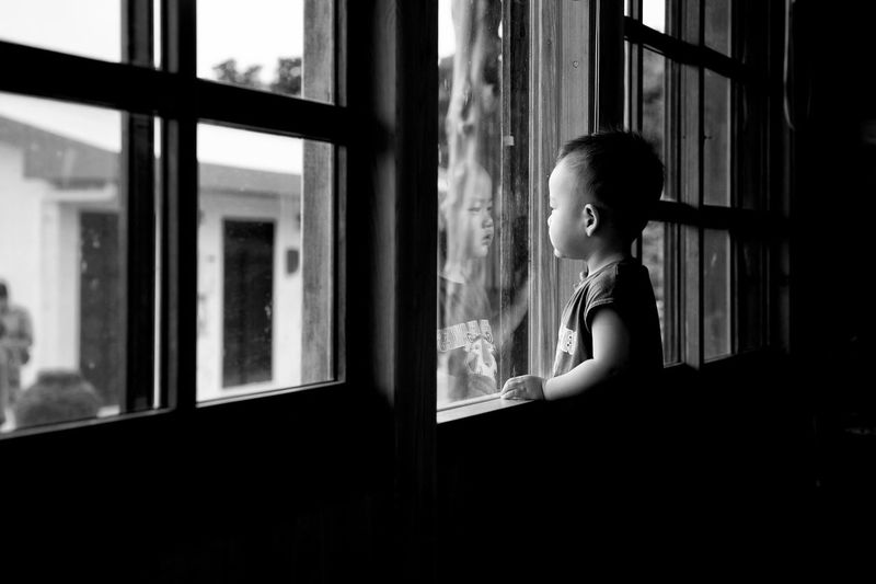 waiting mom Longing Yearning Waiting Gray Blackandwhite Son Japan Moments Mom Window One Person Indoors  Real People Looking Lifestyles Looking Through Window Side View Young Adult Standing Contemplation