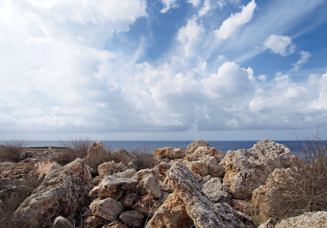 rough rocks and boulders with dry summer vegetation in front of a calm sea with white sunlit clouds filling the sky Sea Rock Water Rock - Object Solid Sky Cloud - Sky Scenics - Nature Horizon Over Water Horizon Tranquility Beauty In Nature Tranquil Scene Nature No People Land Day Beach Outdoors Rocky Coastline Groyne