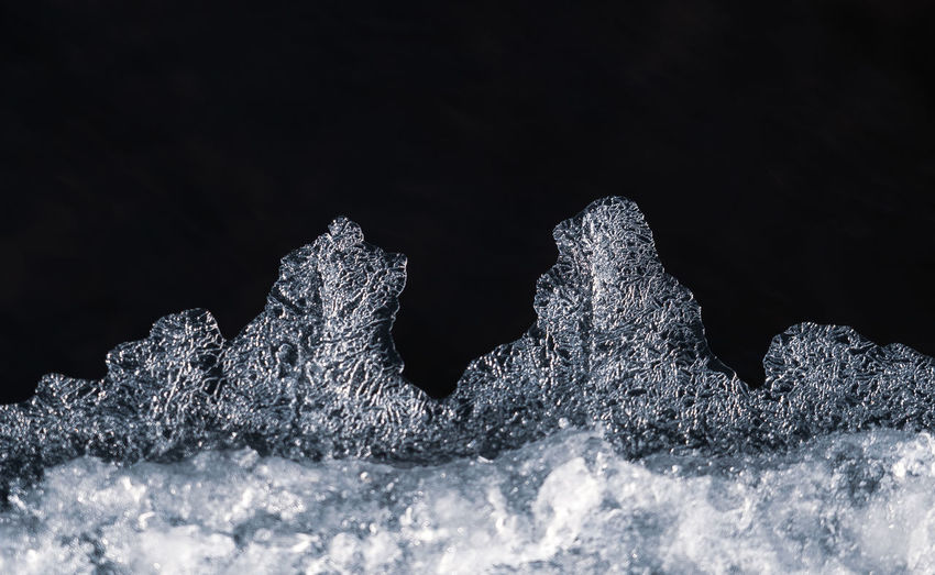 Close-up of frozen water against black background