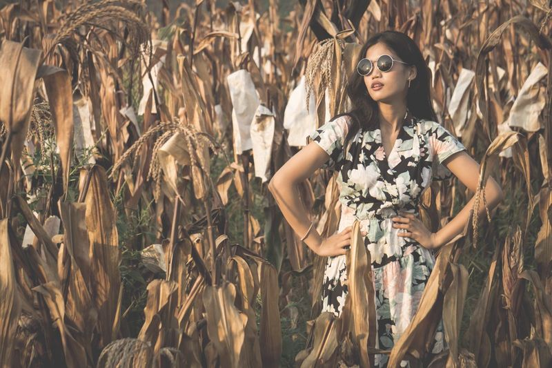 Fashionable young woman with hands on hip standing amidst plants on field