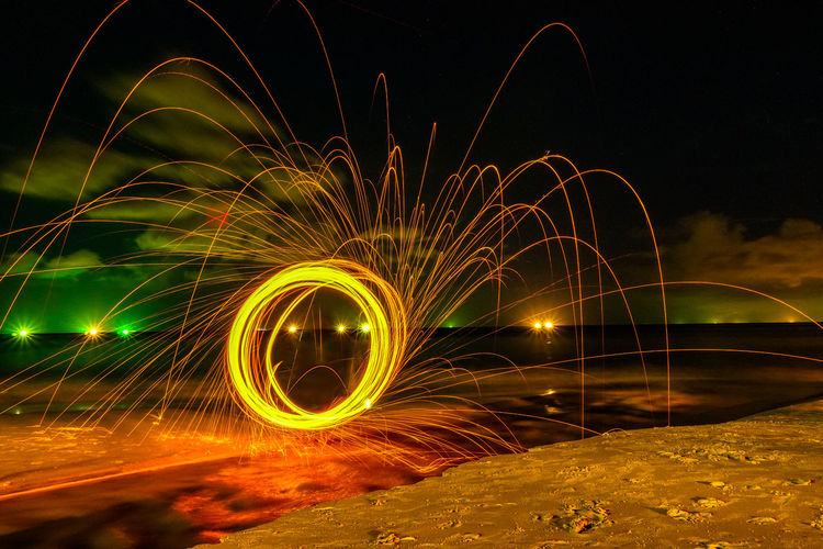 steel wool on the beach look like angry face Night Motion Illuminated Long Exposure Wire Wool Blurred Motion Glowing Spinning Circle Nature Speed Geometric Shape Outdoors Light Trail Sparks Steel Wool, Fire Work, Heart Shape Smile Angray Shape Light - Natural Phenomenon Pattern Light Painting Sky Creativity No People Light