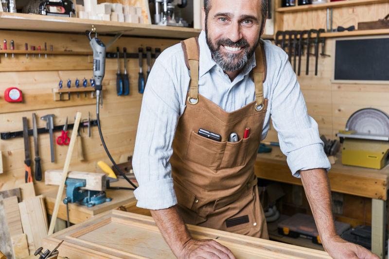 Portrait Of Smiling Carpenter Working In Workshop
