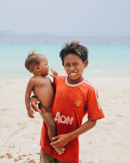 Portrait of boy carrying brother while standing at beach