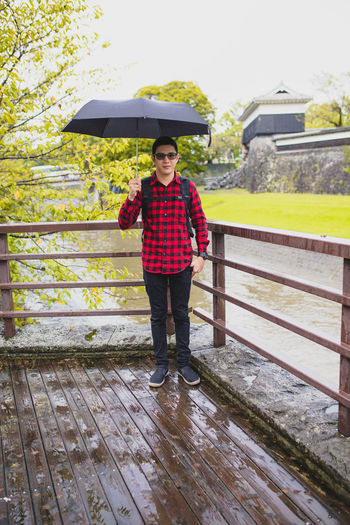 Portrait of man with umbrella standing on bridge during rainy season