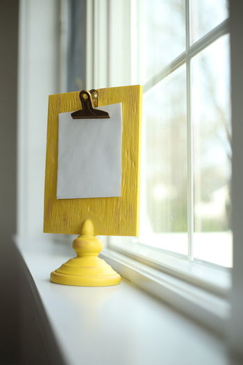 Yellow clipboard with blank space for copy or message. Blank Paper Clipboard Copy Space Indoors  Message Post It Window Windowsill Yellow