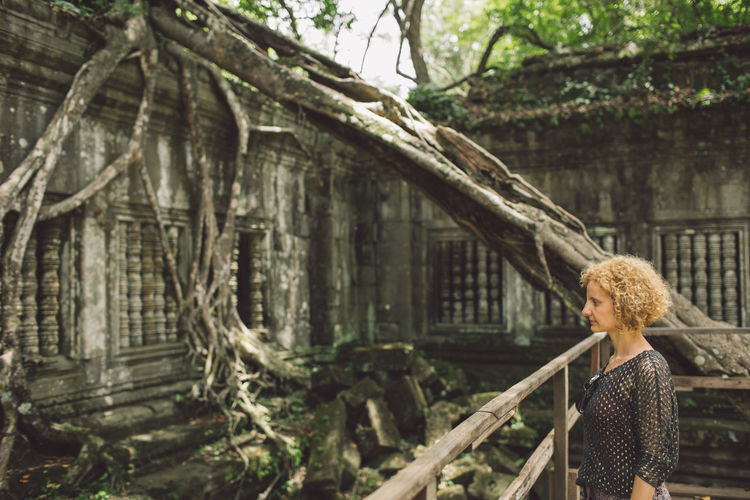 Side View Of Woman At Old Ruins In Forest