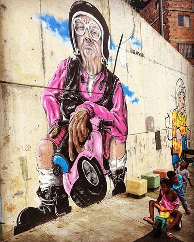 Life imitating art Grafitti Wall City Street City Comuna 13 Street Photography Streetphotography Art Colours Bike Lifeimitatesart Kids Medellín Graffiti Art Graffiti Street Art People Sitting Men Outdoors Multi Colored City Day