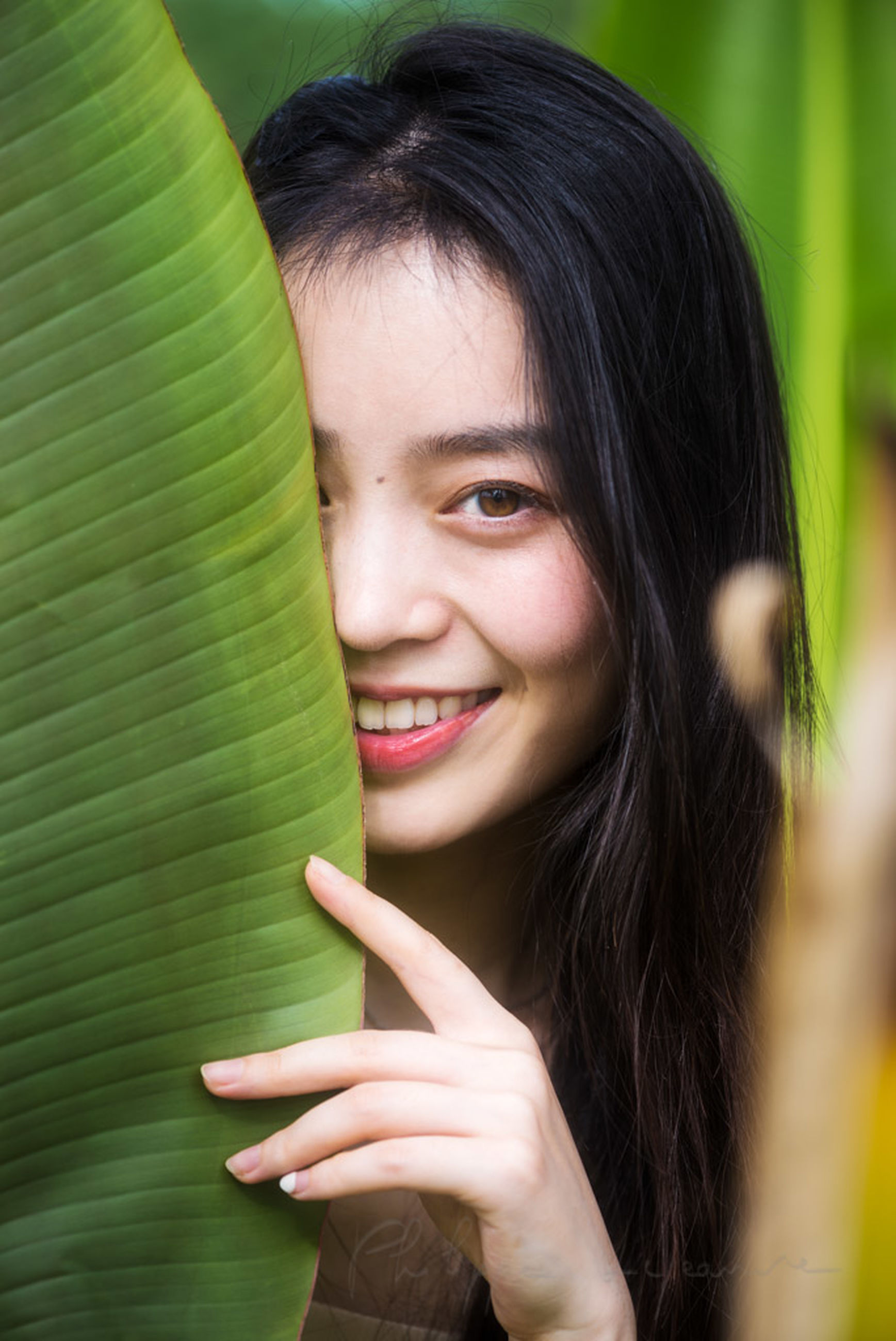 smiling, portrait, one person, happiness, green, women, close-up, female, adult, portrait photography, skin, cheerful, teenager, emotion, long hair, person, human face, hairstyle, looking at camera, young adult, headshot, photo shoot, teeth, smile, black hair, human eye, positive emotion, hand, nature, leaf, lifestyles, human head, child, plant, cute, brown hair, plant part, holding, outdoors, enjoyment, joy, human hair, childhood