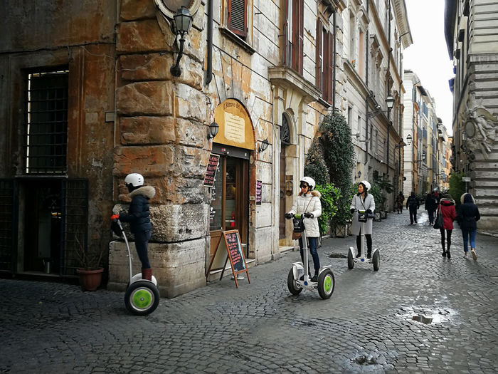 Rome, Italy - March 18, 2018: Three tourists and their guide through the alleys of the center of Rome with the segway, a two-wheeled electric vehicle. City Life Electric Electric Drive Moving Around Rome Transport Architecture Bicycle Building Exterior Built Structure City Day Full Length Lifestyles Men Mobility Mobility Scooter Outdoors People Real People Segway Street Two Wheels Two-wheeler Urban Women