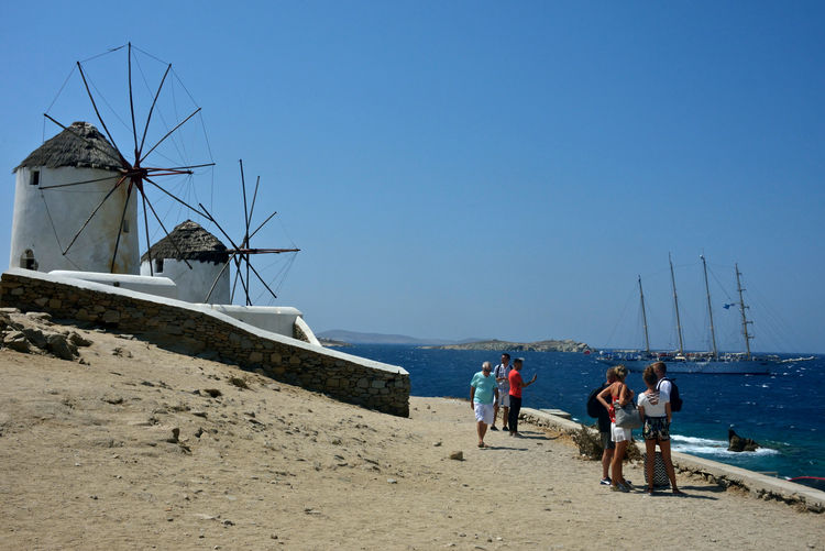 panoramic view with windmills, people and a sailing ship in the blue sea Sky Water Land Beach Sea Environmental Conservation Renewable Energy Men Nature Alternative Energy Fuel And Power Generation Real People Group Of People Day Transportation Clear Sky Wind Turbine Turbine People Horizon Over Water Windmills Mykonos,Greece Chora Highlights Landscape Tourism Destination Summertime Travel Relaxing