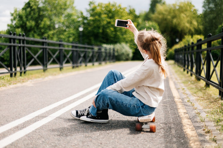 Cute blonde teenage girl sitting on a skateboard in a city park chatting on a smartphone