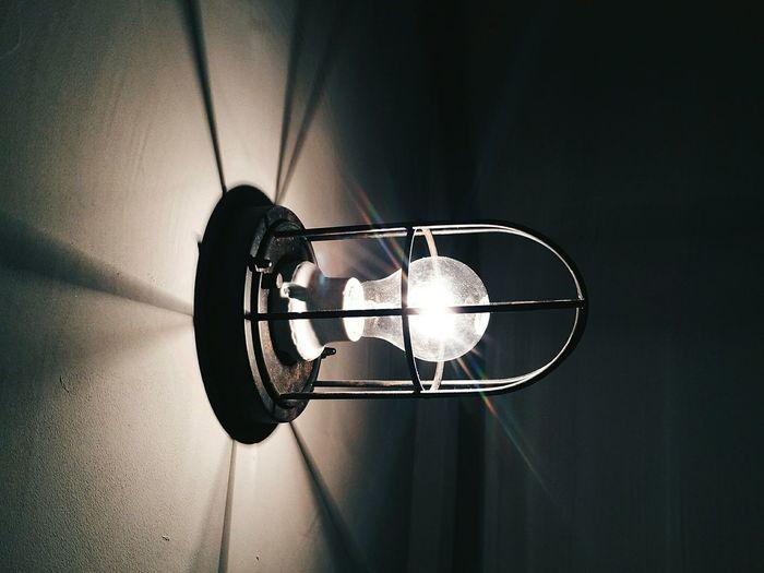 Close-up of illuminated light bulb mounted on wall