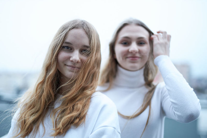 Portrait of smiling young girls standing against white background