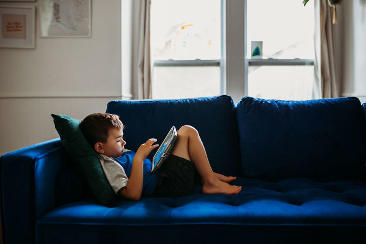 Rear view of boy sitting on sofa at home
