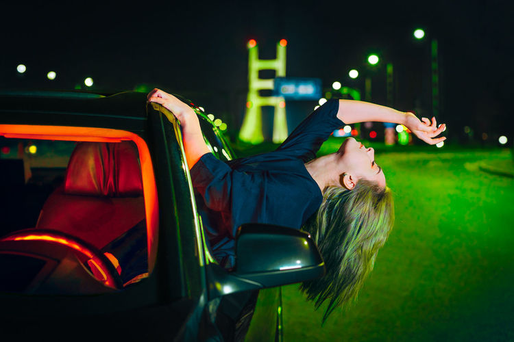Woman in illuminated clothing in the car at night