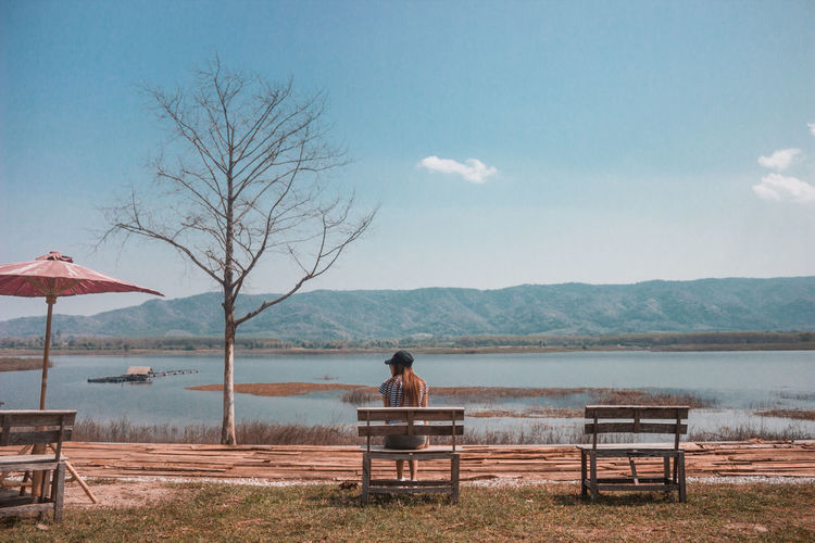 Rear View Of Young Woman Sitting On Bench By Lake Against Sky