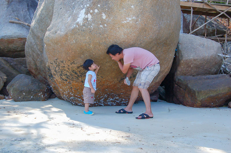 Father and son talking by rocks at beach