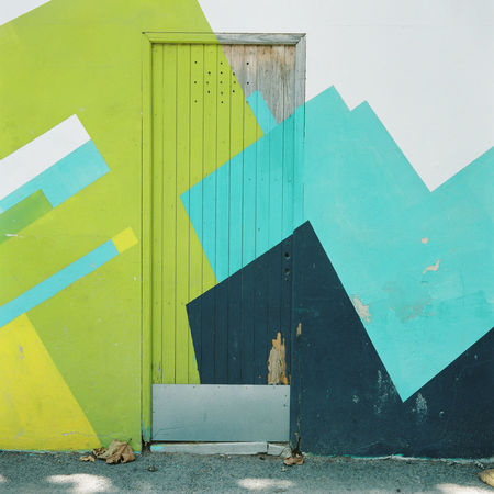Abstract artwork envelops the walls and door of a building in the Majorcan town of Pollença. Abstract Architecture Baleares Balearic Islands Blue Building Exterior Built Structure Colorful Colors Colours Day Door España Film Green No People Outdoors Paint Pollença Quirky Shade SPAIN Summer Wall Yellow