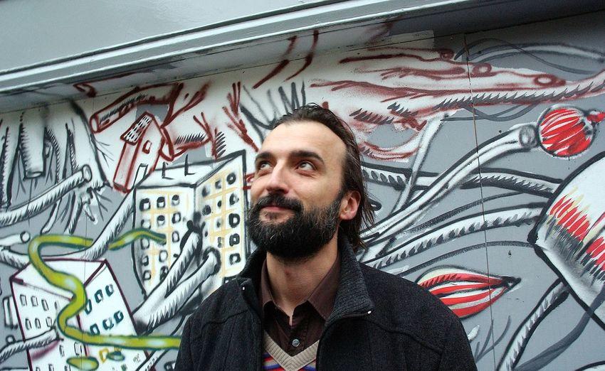 Thoughtful Man Standing Against Graffiti Wall