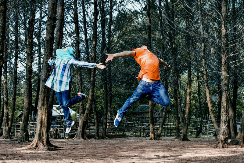 Feeling Free Tree Full Length Plant Men Mid-air Vitality Forest Casual Clothing Nature Leisure Activity Jumping Fun Motion Positive Emotion Land Real People Young Adult Day Side View Togetherness Human Arm WoodLand Jeans Excitement Outdoors Healthy Lifestyle Springtime Decadence