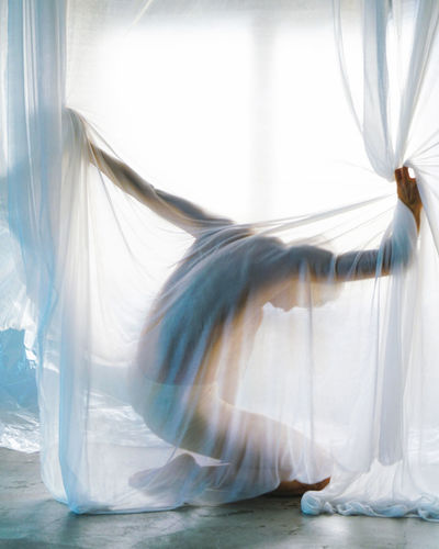 Rear view of woman dancing in curtain