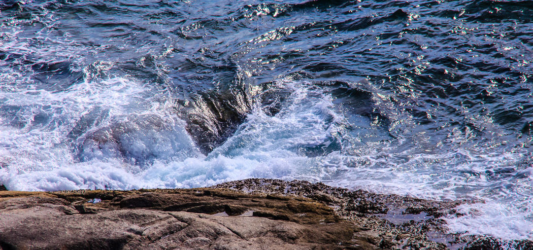 Ocean waves curling and crashing into a rocky shore at sunrise Rocky Beach Rocky Coastline Rocky Shore Beauty In Nature Close-up Day High Angle View Motion Nature No People Ocean Waves Ocean Waves Hits The Rock Ocean Waves On Shore Outdoors Power In Nature Rocky Coast Scenics Sea Water Wave