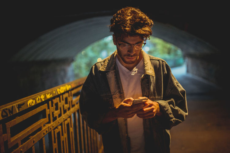 Casual Clothing Communication Connection Focus On Foreground Front View Holding Leisure Activity Lifestyles Mobile Phone Night One Person Outdoors Real People Standing Technology Telephone Using Phone Young Adult Young Men
