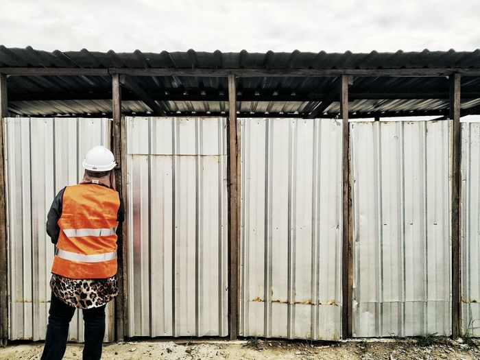 Rear view of worker standing against corrugated iron doors