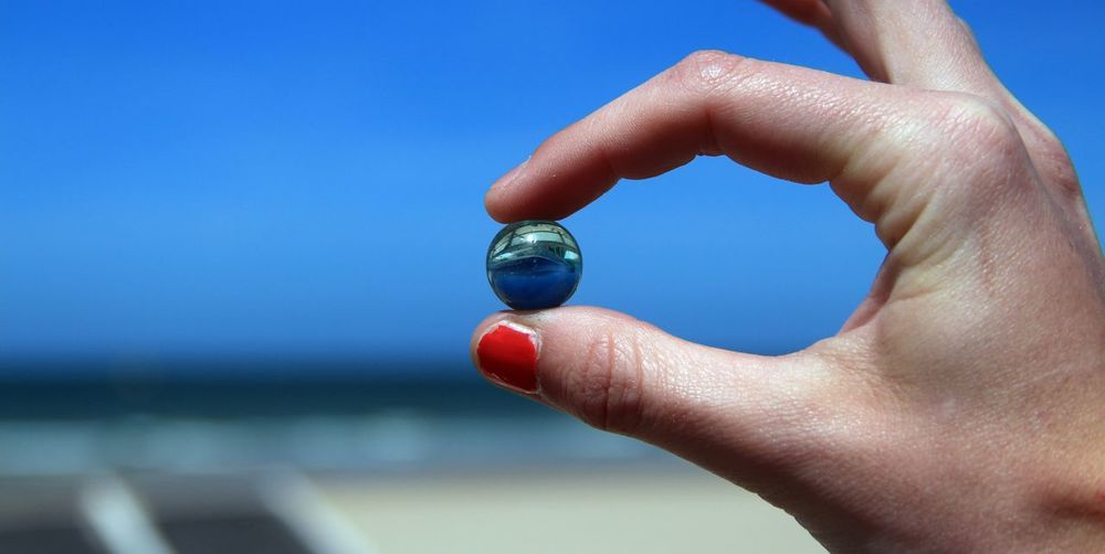 Cropped Hand Of Woman Holding Marbles Against Blue Sky