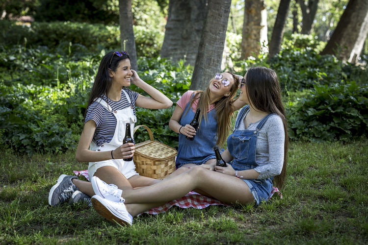 Happy Women Sitting On Grassy Field At Park