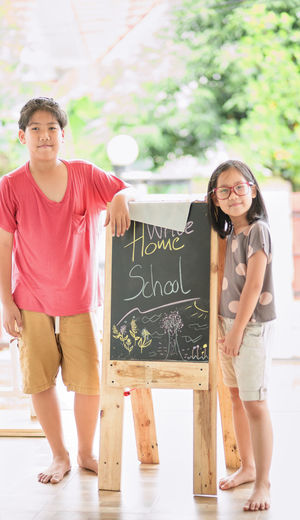 Portrait of smiling kids standing by board outdoors