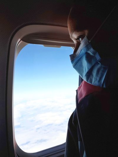 Portrait of person looking through airplane window