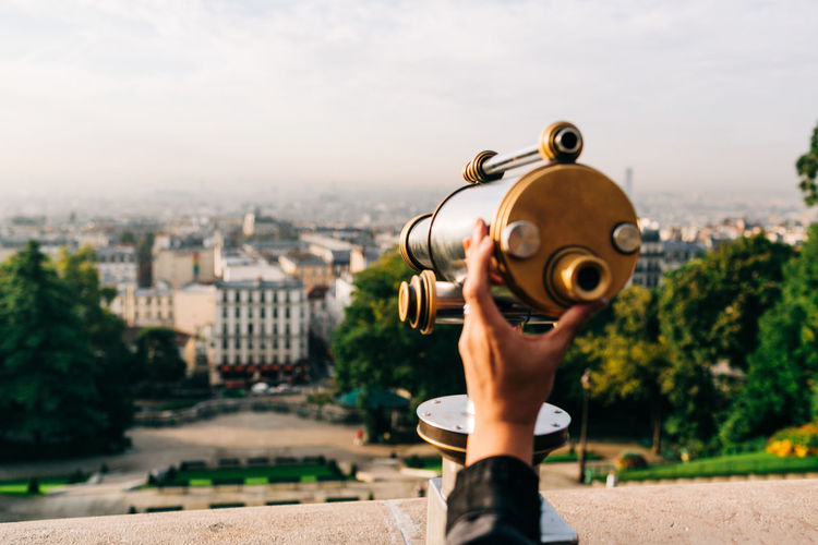 Cropped image of hand holding telescope over cityscape against sky
