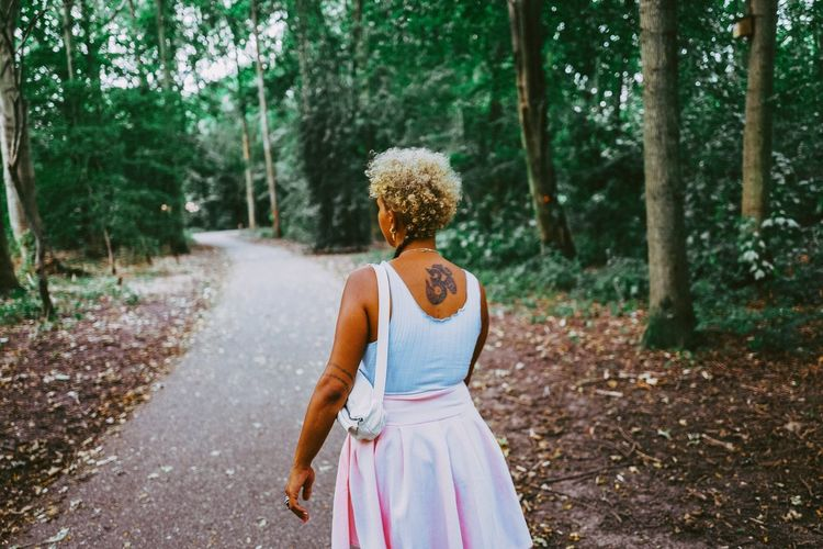 Full length of woman on road amidst trees in forest