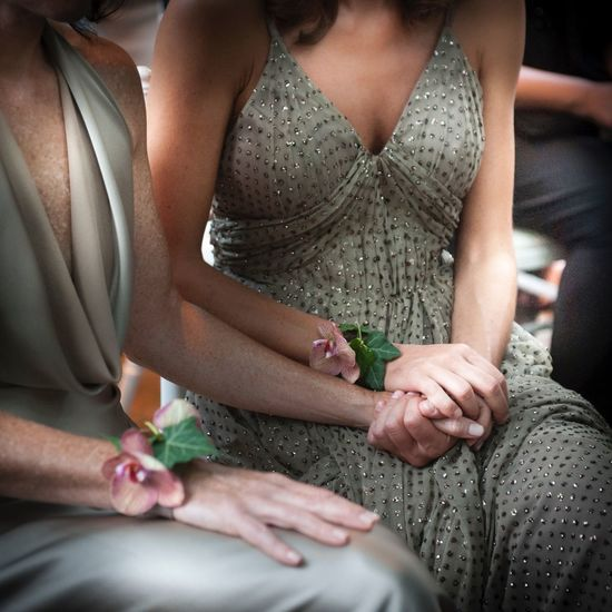Midsection of lesbian couple holding hands during wedding