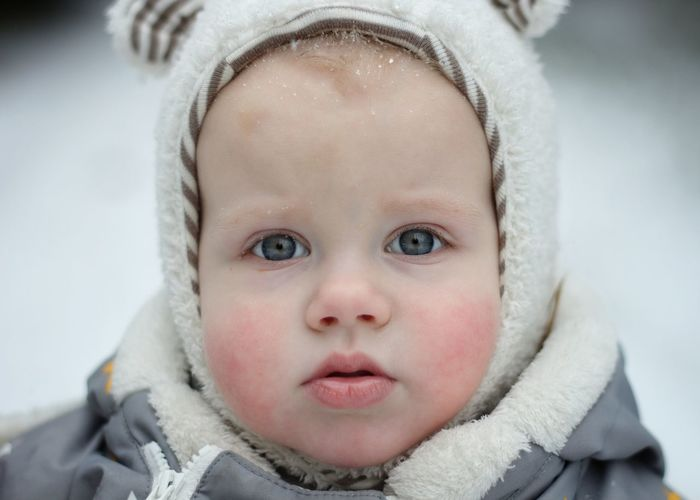 Close-up portrait of cute baby in snow
