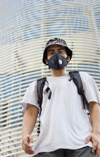 Man wearing a protective mask to avoid coronavirus infection looking straight wearing a bucket cap.