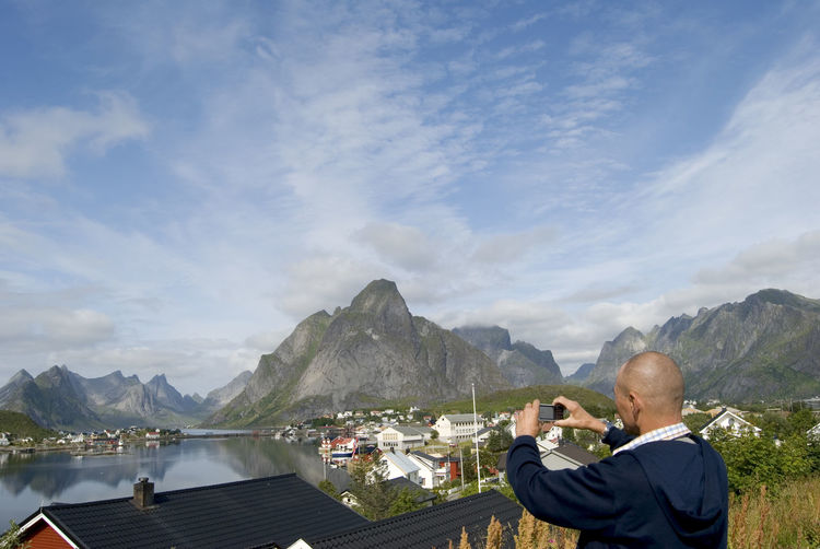 Man Photographing Lake And Mountains From Mobile Phone