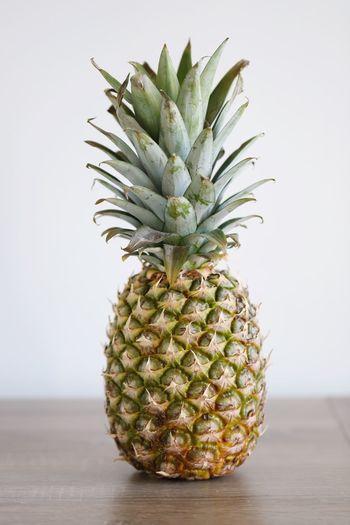 Hello my names is mista pineapple EyeEm Selects Pineapple Tropical Fruit Healthy Eating Indoors  Still Life Fruit Table Studio Shot Food Food And Drink Wellbeing Freshness Green Color Natural Pattern Spiked Single Object White Background Close-up No People Wall - Building Feature