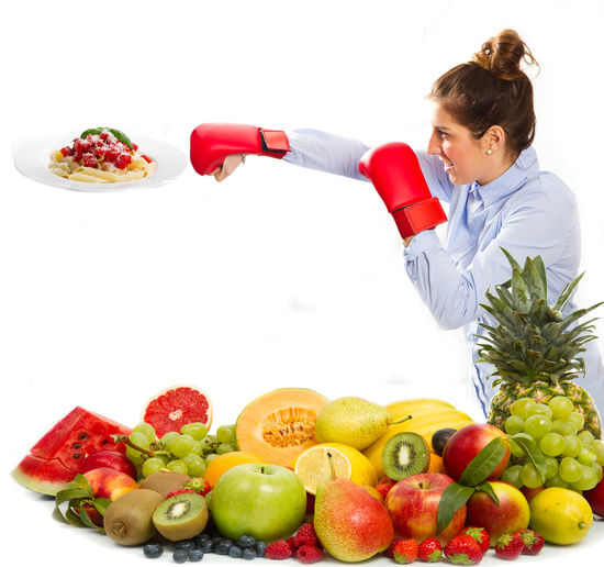 Young Businesswoman Practicing Boxing By Food Against White Background