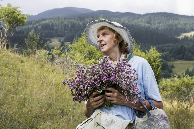 Portrait of smiling woman standing on field and holding oregano herbs flowers