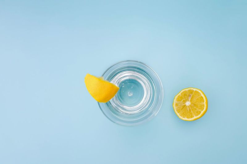 Cooling  Lemon Water Water Lemons Fruit Citrus Fruit Healthy Eating Food And Drink Food Still Life Wellbeing Freshness Lemon Colored Background SLICE Drink Blue Directly Above Yellow Glass