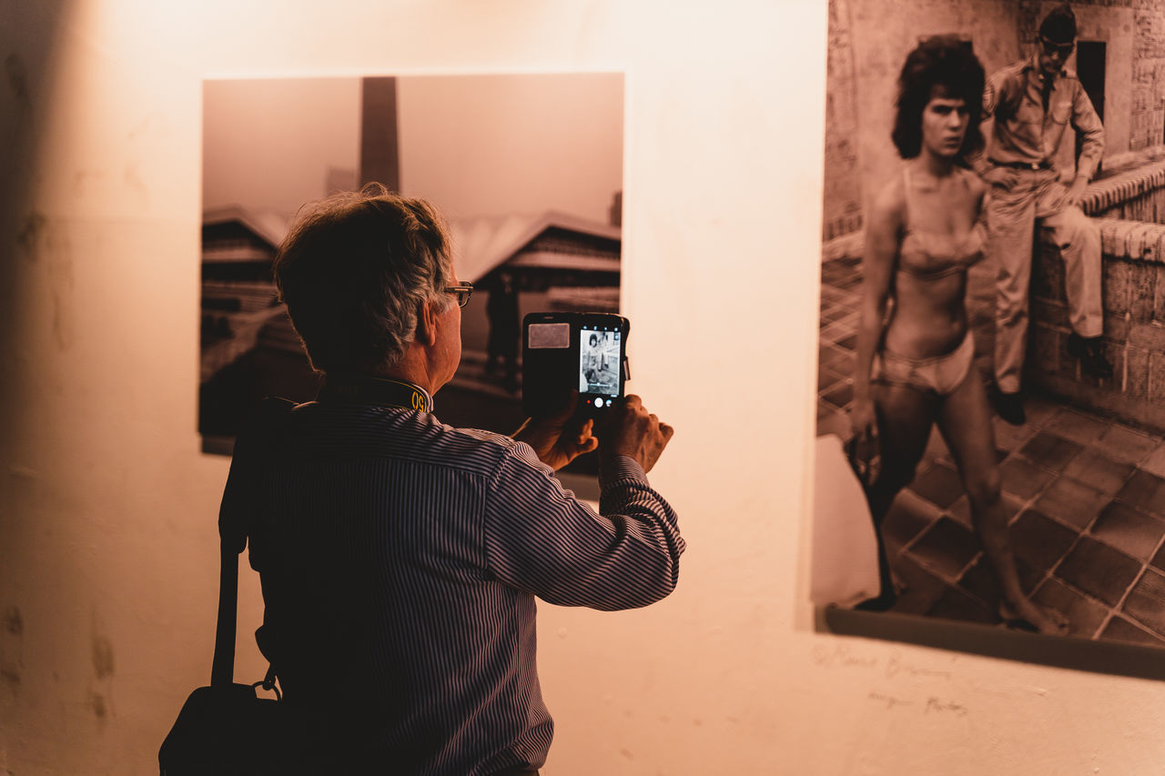 REAR VIEW OF MAN PHOTOGRAPHING AT HOME