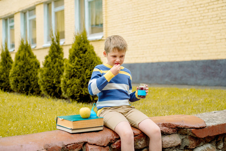 Boy eating food while sitting outdoors