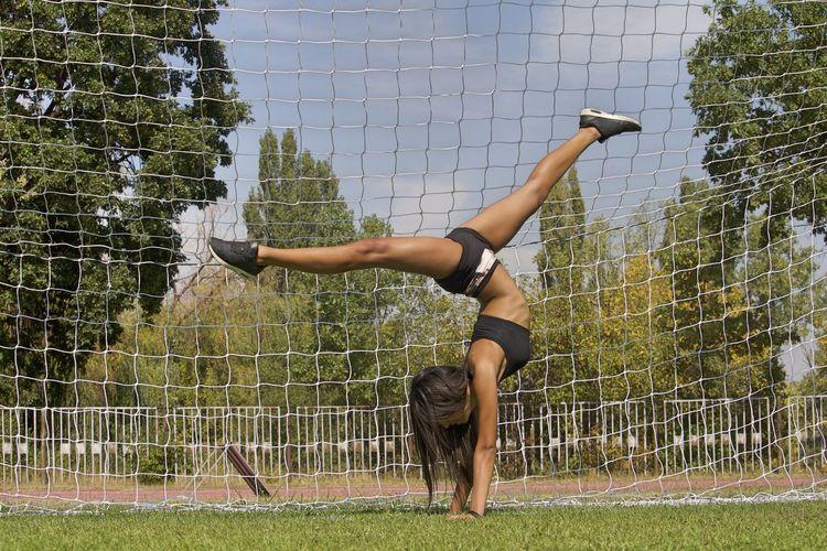 Full length of woman doing handstand against net