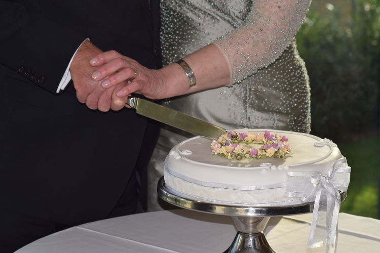 Midsection Of Couple Cutting Cake On Table