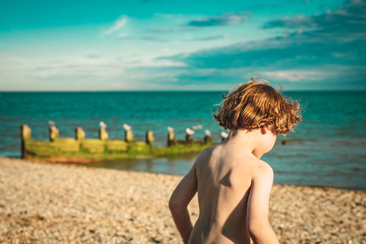 Boy playing on the beach on a sunny day