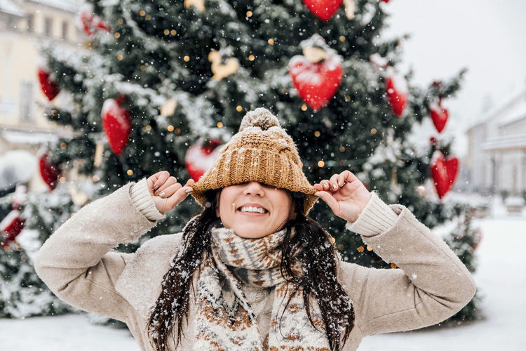 Portriat of young woman pulling her hat over her eyes, happy, smiling, winter, christmas, snowing.