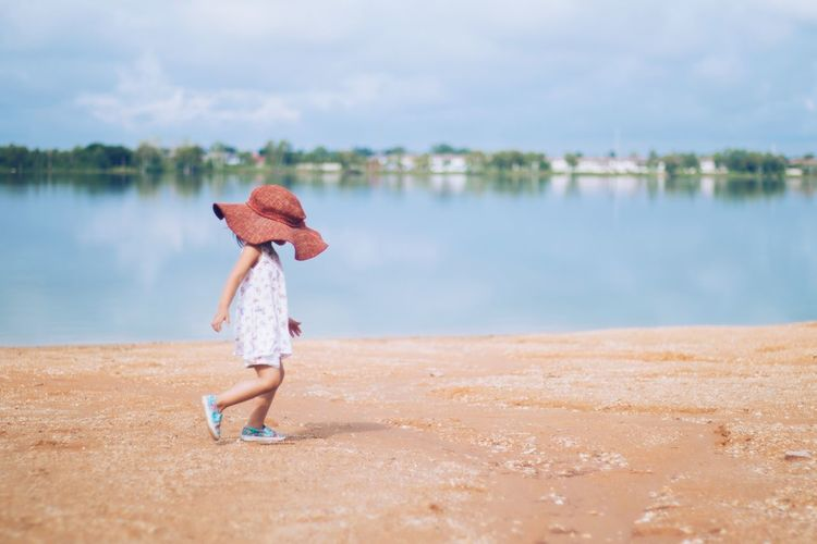 Beach Child Childhood Children Only Day Full Length Hat Hat Lake Leisure Activity Nature One Person Outdoors People Side View Sky Straw Hat Style And Fashion Summer Vacations Walking Around Water