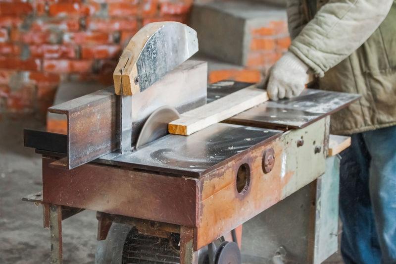 A carpenter cuts wood with a circular saw in a carpenter's shop